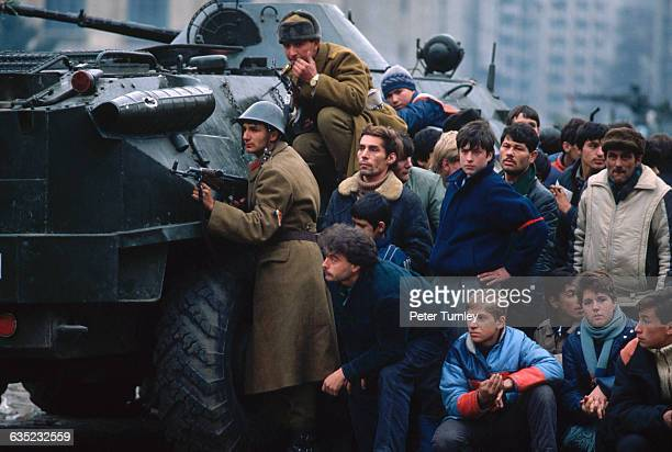 During the 1989 revolution Romanian soldiers and civilians take cover behind a tank in Bucharest's Palace Square