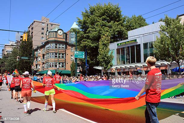 During the August 4th, 2013 Vancouver Gay Pride Parade, along Robson Street, volunteers are carrying a huge rainbow flag, symbol of lesbian, gay,...