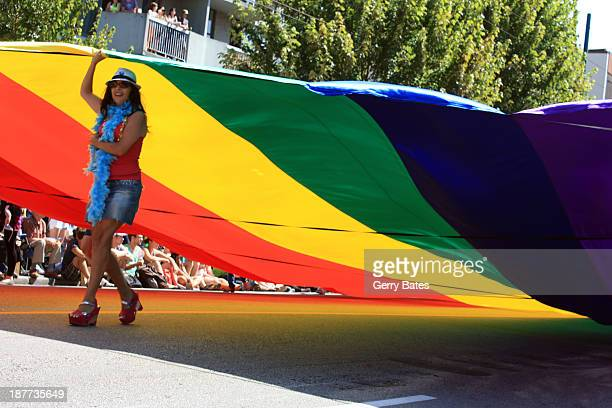 During the August 4th, 2013 Vancouver Gay Pride Parade, along Robson Street, this participant is one of several people carrying a huge rainbow flag,...