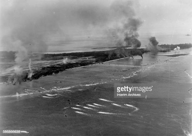 During the Battle of Peleliu smoke rises as US Navy Amphtracs also known as a LVT push past the coral reef on their way to the beaches of Peleliu...
