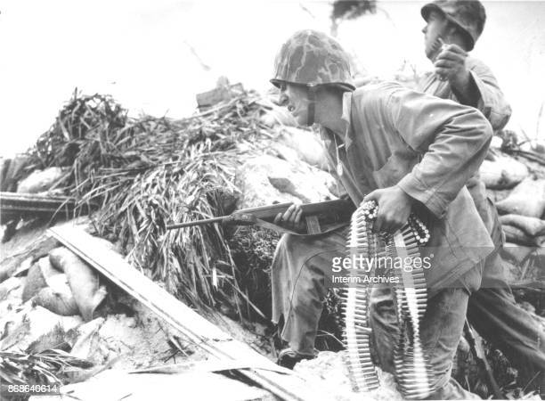 During the Battle of Tarawa a United States Marine an ammunition belt in one hand and a carbine rifle in the other as he crouches beside a soldier...