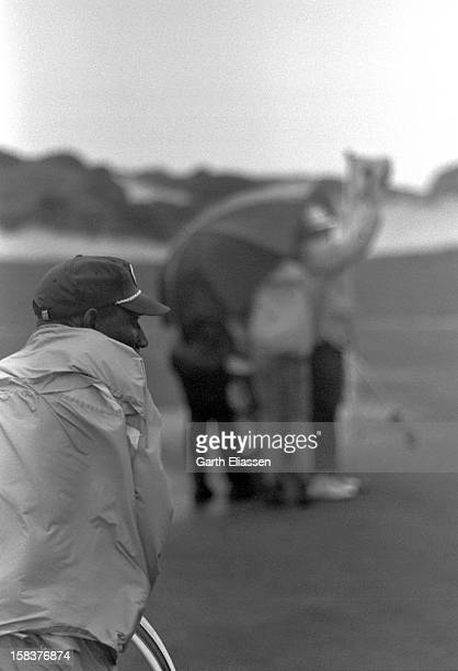 During the Bing Crosby National ProAmateur golf tournament a caddie clutches a golf bag as golfers huddle against the wind on the 16th hole of the...