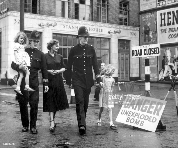 During the blitz police officers and area citizens walk by a sign that reads 'Danger Unexploded Bombs' and 'Road Closed' in London early to mid 1940s