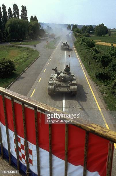 During the civil war in Slovenia a convoy of the Yugoslavian Federal Army travels in position with T55 and T72 tanks through rural agricultural...
