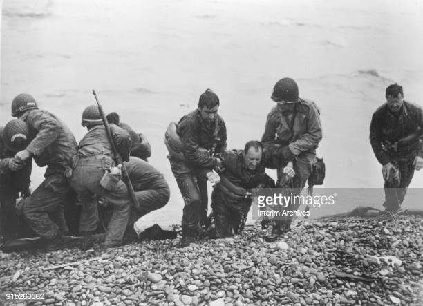 During the DDay landings American soldiers pull survivors from a sunken landing craft onto shore at Omaha Beach Normandy France June 6 1944