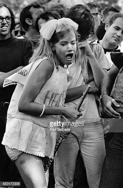 During the Democratic National Convention protests a female protestor with a flute stands with other demonstrators gathered at Lincoln Park Chicago...