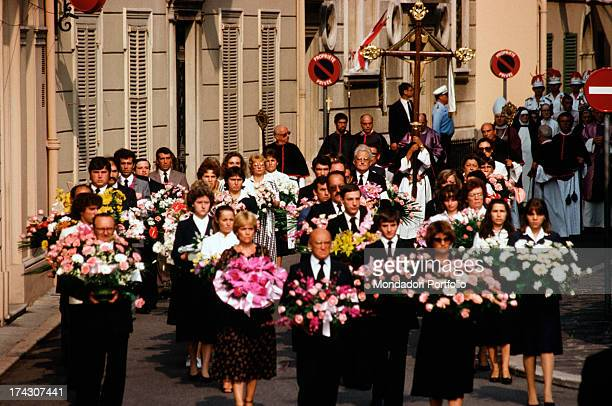 During the funeral of Grace Kelly some carabinieri wearing uniforms aid a woman after her fainting taking her on their arms all around them...