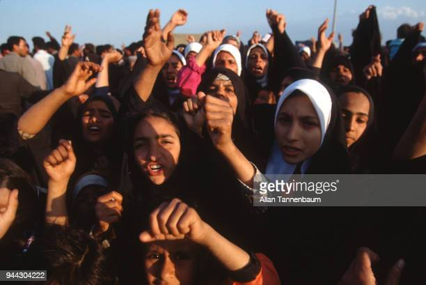 During the Gulf War a large group of women arms in the air shout in a refugee camp Iraq 1991