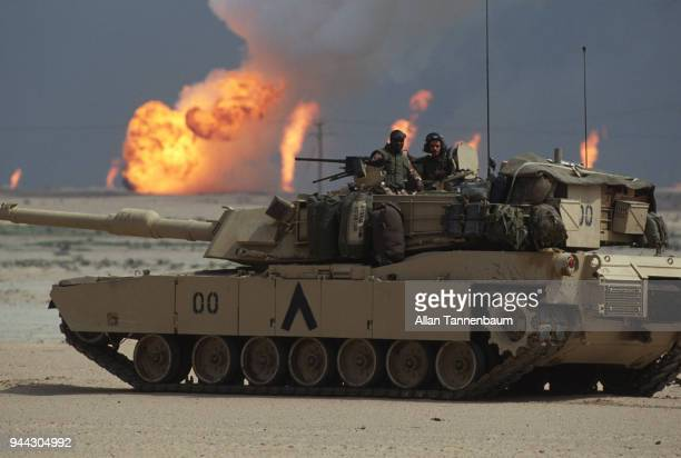 During the Gulf War a pair of American soldiers stand in the turret of an M1A1 Abrams tank as near the border with Iraq oil wells burn in the...