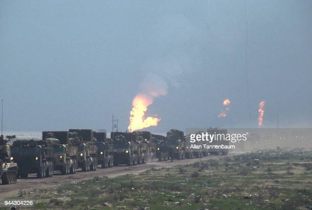 During the Gulf War American military vehicles drive along a road as oil wells burn in the background Iraq 1991