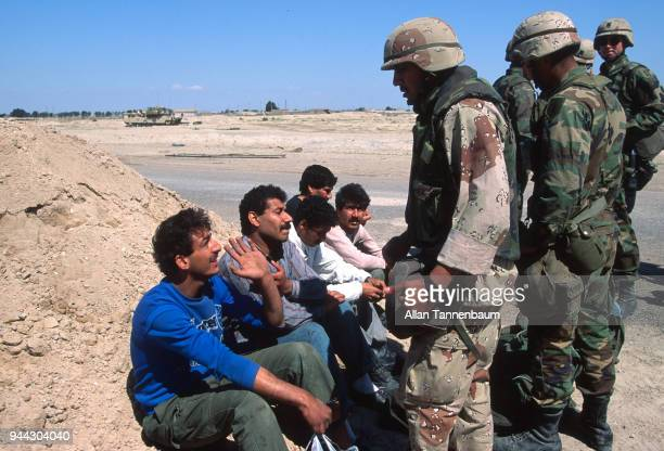 During the Gulf War American soldiers question a group of men who sit by the side of a road at a checkpoint Iraq 1991