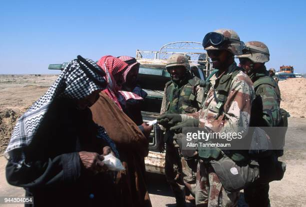 During the Gulf War American soldiers smile as they examine the documents of a trio of men at a checkpoint Iraq 1991