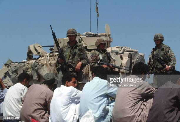 During the Gulf War American soldiers stand guard over a group of men seated at a checkpoint Iraq 1991