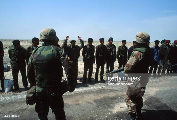 During the Gulf War American troops guard Iraqi soldiers who stand at the side of a road after their surrender Iraq 1991