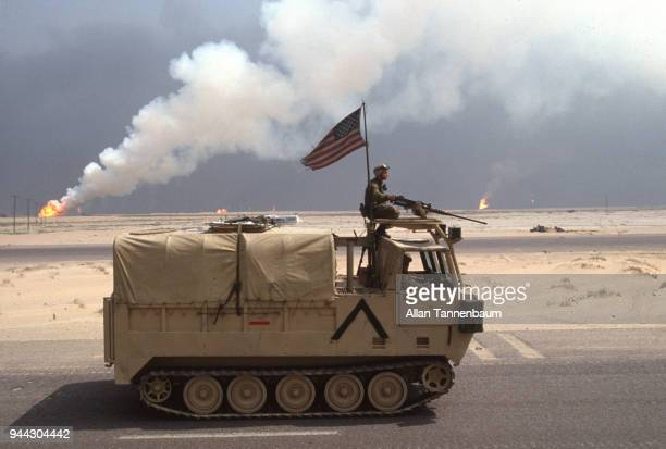 During the Gulf War an American M548 Tracked Cargo Carrier with a gunner on the roof drives past oil wells that burn in the distance Kuwait 1991