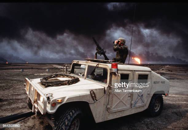 During the Gulf War an American soldier looks through binoculars from atop a Military Police Humvee as wells in Al Ahmadi oil field burn in the...