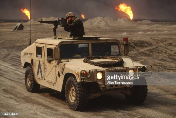 During the Gulf War an American soldier mans a machine gun atop a Humvee while oil wells burn in the background Kuwait 1991