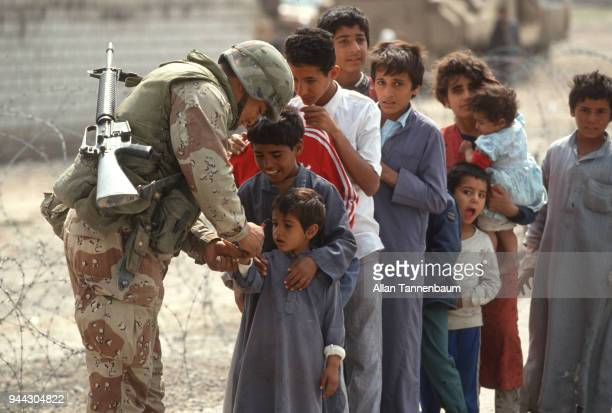 During the Gulf War an American soldier writes something on the hand of a young boy at the head od a line of children Iraq 1991