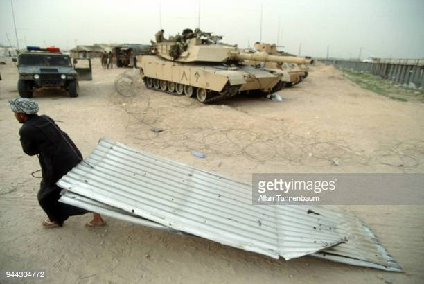 During the Gulf War an Iraqi man drags a sheet of corrugated steel past a line of tanks at a refugee camp Iraq 1991