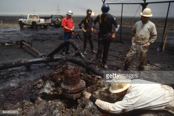 During the Gulf War oil workers watch as an Army engineer examines a well head Kuwait 1991