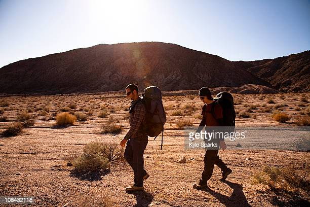 During the heat of the midday sun, two male hikers backpack through Death Valley's Confidence Hills, California.