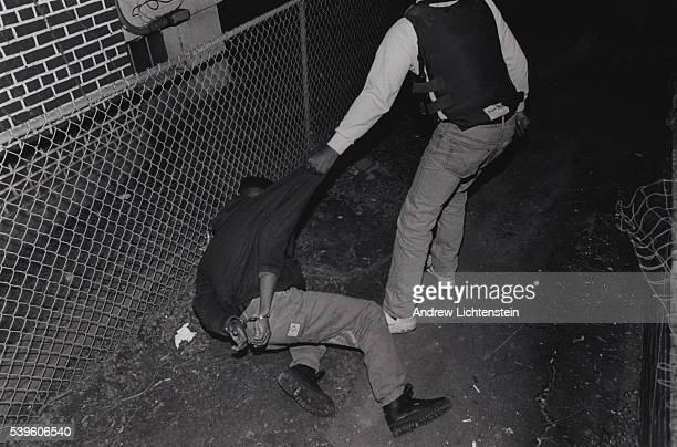 During the height of the crack epidemic in Bridgeport CT a narcotics officer hauls a prisoner arrested in a raid on crack hose off to a waiting...