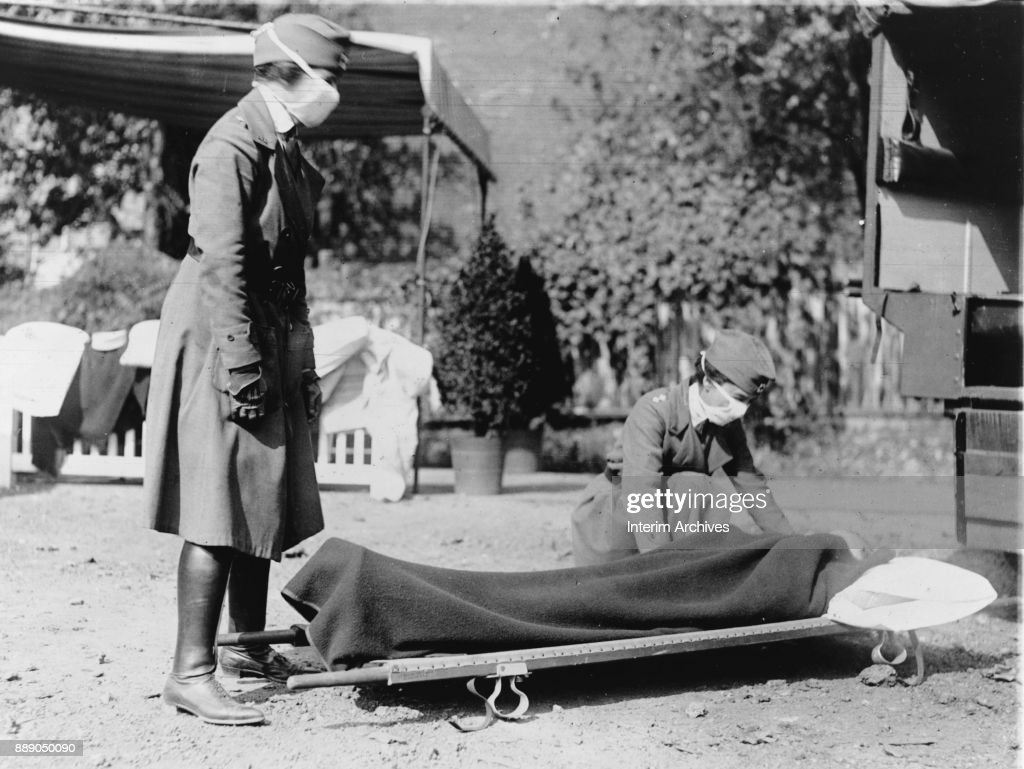 During the influenza epidemic, members of the Red Cross Motor Corps, both in uniform with cloth face masks, beside a stretcher on the ground, Washington DC, 1918.