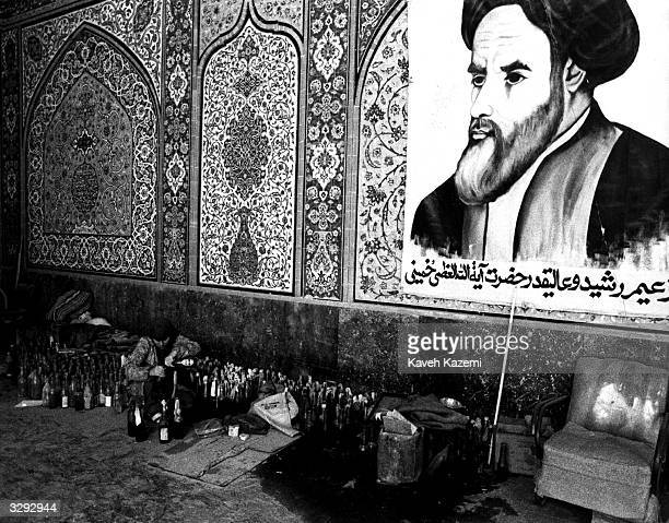 During the IranIraq War a young woman makes Molotov cocktails for the Pasdarans in the mosque at Abadan 10th December 1980 A large poster of the...
