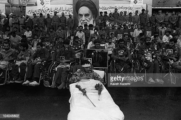 During the IranIraq War disabled veterans of the Iranian Revolutionary Guard Corps hold pictures of Ayatollah Khomeni on Pasdaran's Day which...