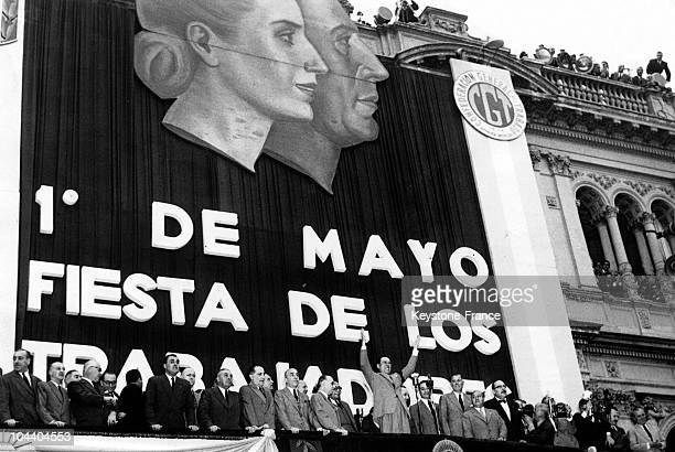 During the Labour Day celebrations Argentinian President Juan PERON salutes the crowd from a balcony of the government building Near him are members...