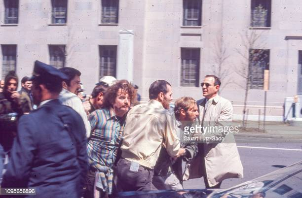 During the May Day protests against the Vietnam War in Washington DC a protester lunges forward as he is retrained by two men in plain clothing...