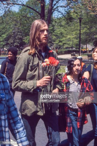 During the May Day protests against the Vietnam War in Washington DC protestors in hippie attire march hand in hand as one man holds a vase of...
