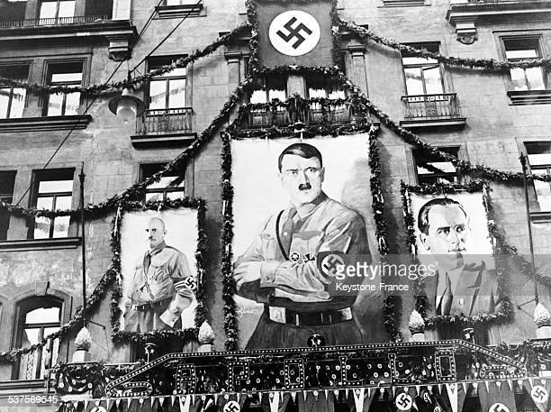 During the National Socialist Congress in Nuremberg we an see on the Apollo theatre's facade three portraits Adolf Hitler at the centre Frank...