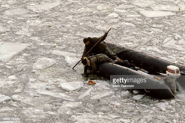 During the salvage operation after the Air Florida Flight 90 crash two men on an inflatable motorboat reach into the frozen Potomac River Washington...
