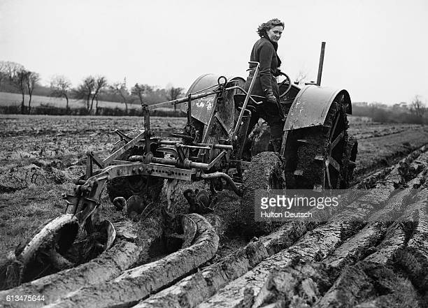 During the Second World War Land Army girl 21 year old Peggy Ayres of Watford who used to work in a printing factory hauls a single furrow plough on...