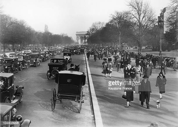 During the springtime in Paris in March 1929, crowds of Parisians headed by foot or by car to the Bois de Boulogne via avenue Foch. One can notice...