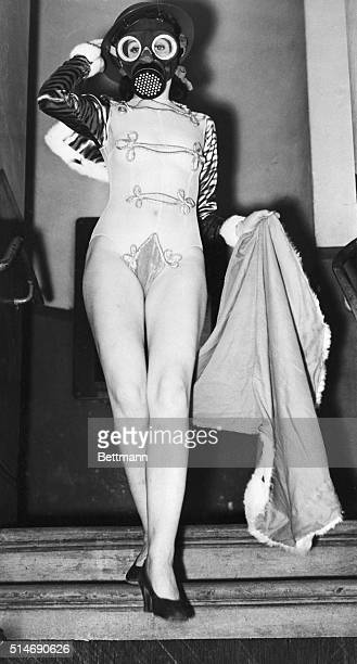 During the tension of World War II a revue has dressed one of their showgirls in a gas mask and helmet in addition to a sexy outfit