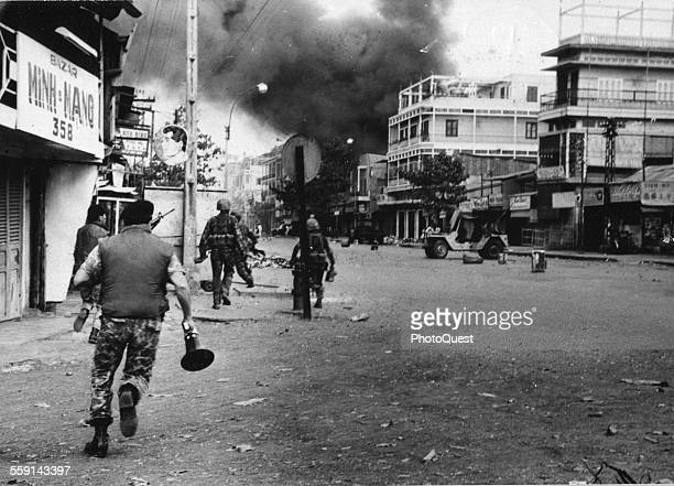 During the Tet Offensive Vietnamese troops move along a street towards billowing smoke from a building attacked by Viet Cong soldiers Saigon Vietnam...