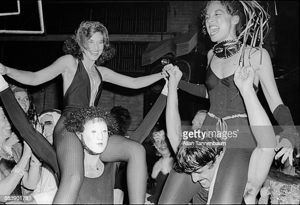 During the third annual Halloween party at Studio 54 costumed women laugh atop the shoulders of their male companions New York New York October 31...