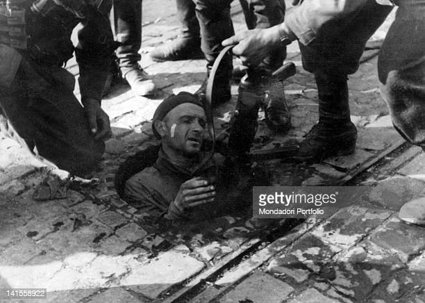 During the Warsaw uprising a Polish rebel comes out of a sewage cover and is captured by German soldiers Warsaw May 1943