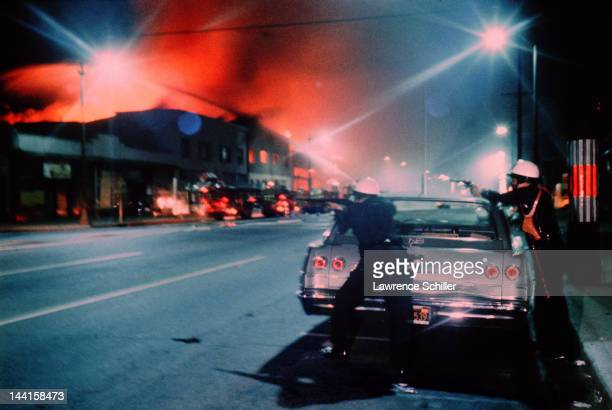 During the Watts Riots two police officers aim from behind a parked car as fire and smoke from a burning building color the night sky Los Angeles...