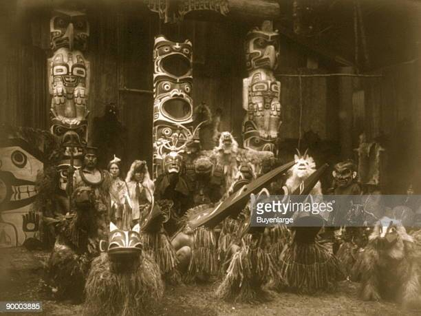 During the winter ceremony Kwakiutl dancers wearing masks and costumes crouch in foreground with others behind them The chief on the far left holds a...