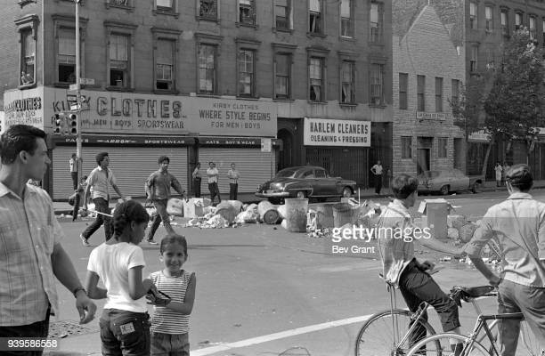 During the Young Lords Party's 'Garbage Offensive,' a number of people stand or walk in front of trash piled on the street and across the...