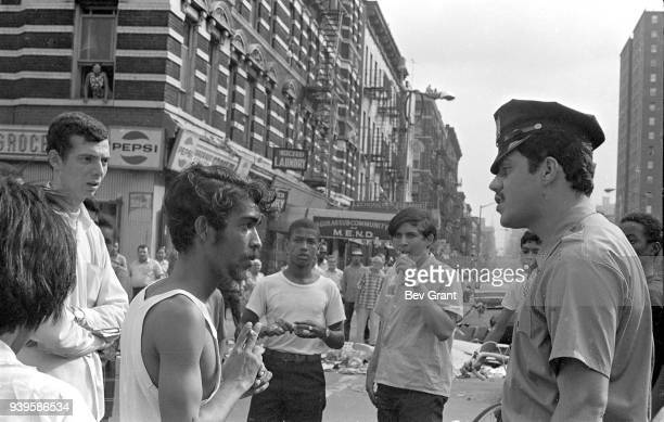 During the Young Lords Party's 'Garbage Offensive,' a police officer talks with community members in the El Barrio neighborhood, East Harlem, New...