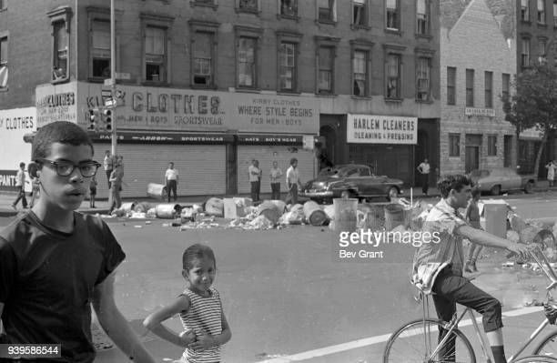 During the Young Lords Party's 'Garbage Offensive,' several children stand in front of trash piled on the street and across the intersection of 3rd...