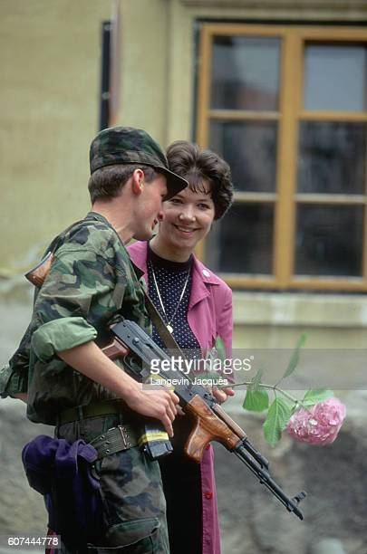 During the Yugoslavian Civil War, government buildings and ministries are guarded by sentries with the Croatian Territorial Army. A civilian woman...