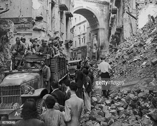 During their advance on Rome American troops of the 5th Army are held up while rubble from bombed buildings is cleared from a street in Naples...
