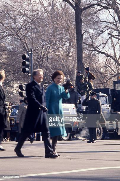 During their Inaugural Parade President Jimmy Carter and First Lady Rosalynn Carter walk past crowded streets Washington DC January 20 1977