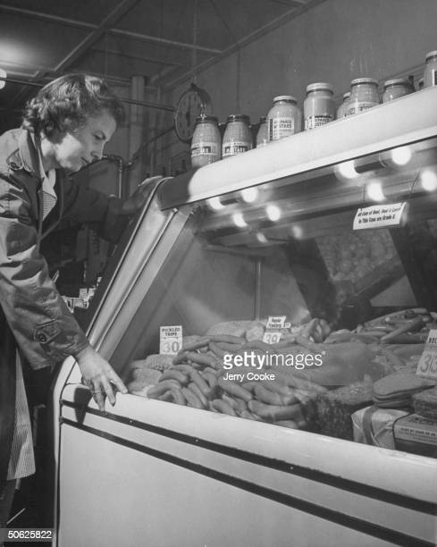During war rationing woman shopping at local market for meat which consists of franks luncheon loaf bologna and tripe
