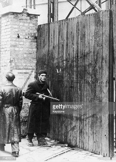 During widespread strikes in the aftermath of the Hungarian uprising a Hungarian worker armed with a machine gun keeps guard on a factory gate on...